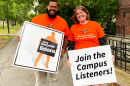 A photo of two New Hampshire Listens staff holding signs encouraging people to join Campus Listeners