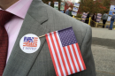 """A man in a suit has a NH """"I voted sticker"""" on his chest as well as an American flag"""