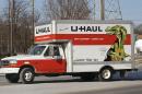 A U-Haul truck drives on a rural, winter road