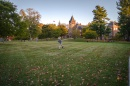 Student walking across lawn, T Hall in the background