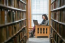 UNH online MBA student studying in the library