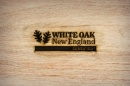 """Logo with leaves and words """"White Oak New England Certified"""" are branded on piece of wood"""