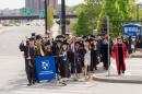 UNH Manchester graduates process up a Queen City street