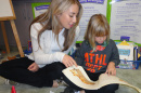 College student reading to younger student in literacy center