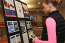 Studnet reading poster at Undergraduate Research Conference