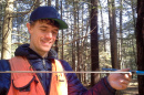 Cameron McIntire, a doctoral student in natural resources and the environment at UNH, cores an eastern white pine