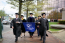 UNH Manchester Commencement participants walking with banner