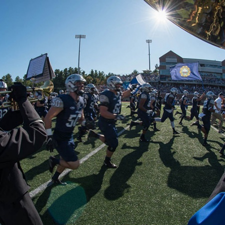 UNH football players and marching band run across the field during the Homecoming 2017 football game