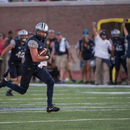 UNH football player running during the homecoming game
