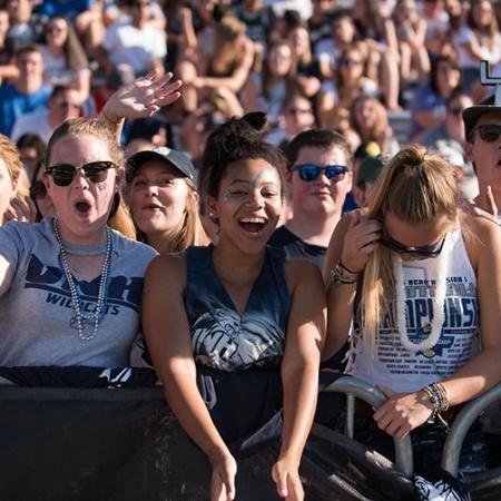 UNH students cheering at the homecoming football game