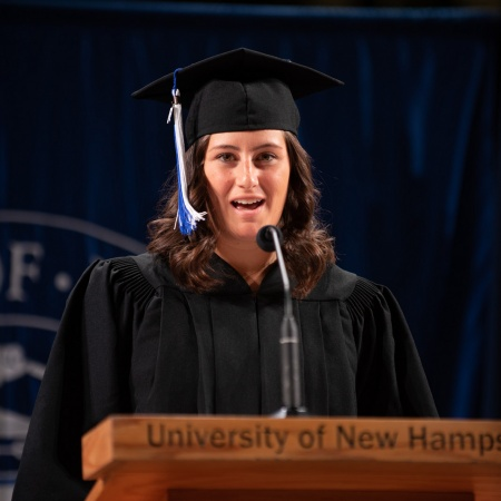 A UNH student receives their cord