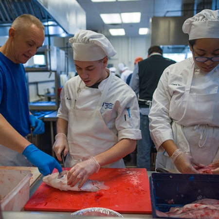 Brad LaMonica and Ciara McCarter from UNH's Thompson School of Applied Science Culinary Arts & Nutrition program get a filet lesson from Rich Pettigrew, owner of Seaport Fish in Rye, N.H.