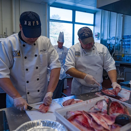Chef Paul Morrison and Chef Jayson McCarter of the N.H. Food Bank's Recipe for Success program help to filet the UNH donated tilapia
