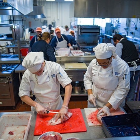 Brad LaMonica and Ciara McCarter from UNH's Thompson School of Applied Science Culinary Arts & Nutrition program filet and bag tilapia