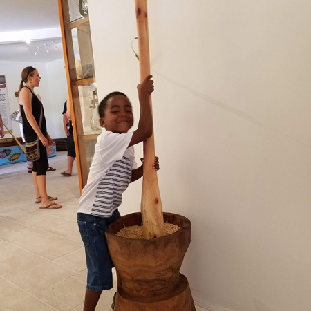 a boy playing with rice pounder