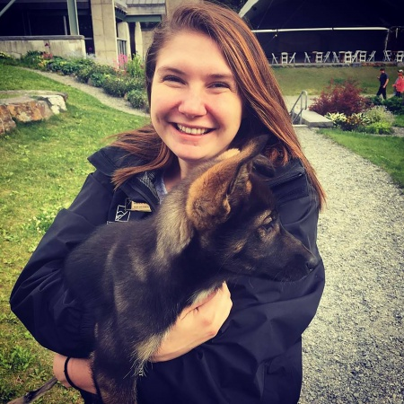 Genevieve Wolfe holds a sled dog puppy