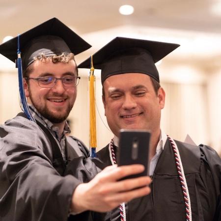 UNH Manchester graduates pose for a selfie