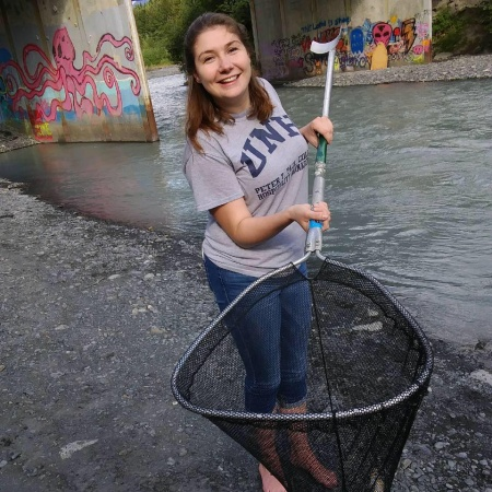 Genevieve Wolfe catching salmon in a net