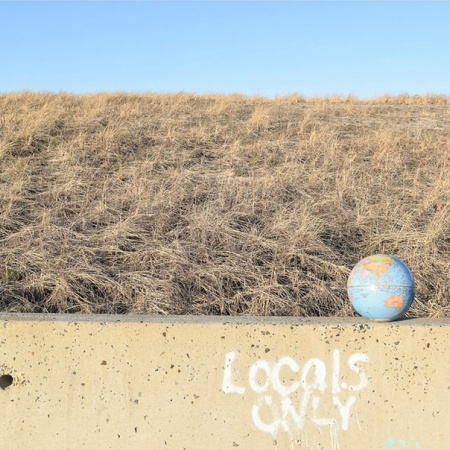 a photo of a globe sitting on a wall in front of a sand dune called Globe #6 by UNH student Alexandra Caggiano '16