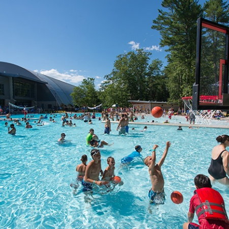 kids playing water basketball at the opening of UNH's new outdoor pool