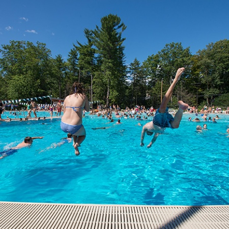 kids jumping into UNH's new outdoor pool at the opening