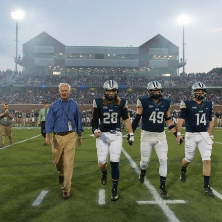 President Mark Huddleston joins three football players as they walk off the field