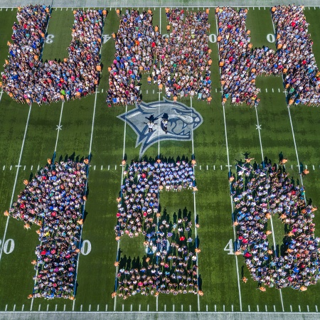 Faculty, staff and students on the football field spelling out UNH 150
