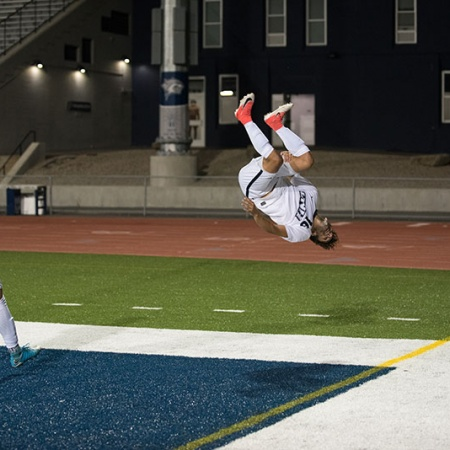 UNH men's soccer player doing a flip