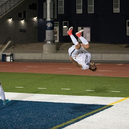 UNH men's soccer player doing a flip