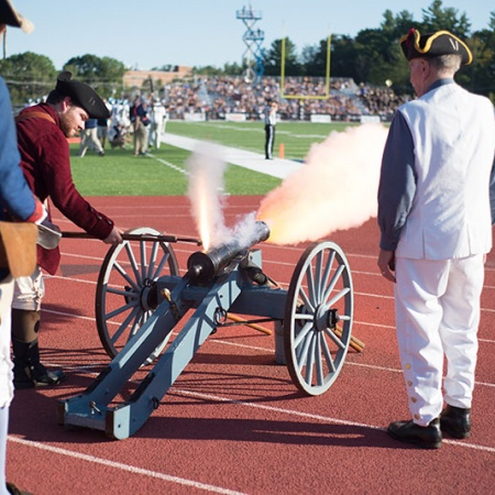 Dick Dewing and crew set off the cannon at a UNH football game