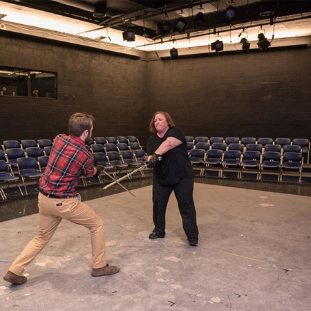 UNH student and professor sparring with swords