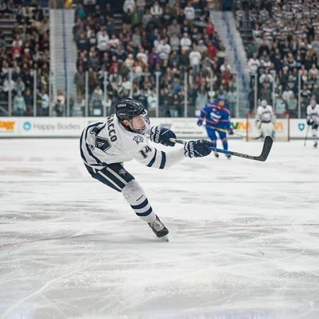 UNH men's hockey player takes a shot