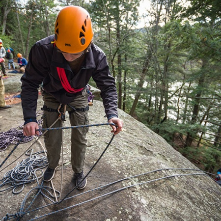 UNH student rappeling down a rock face