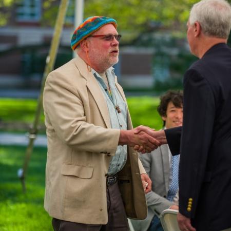 Mark Huddleston shaking the hand of a faculty member