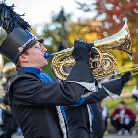 A student playing a horn in the UNH Homecoming Parade