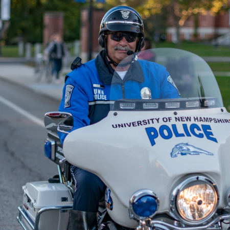 An officer rides a motorcycle in UNH's Homecoming Parade 2018