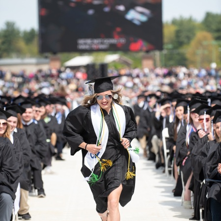 UNH Graduate Elinor Purrier '18 running towards the stage at UNH commencement 2018