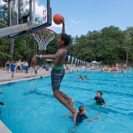kid playing water basketball at the opening of UNH's new outdoor pool