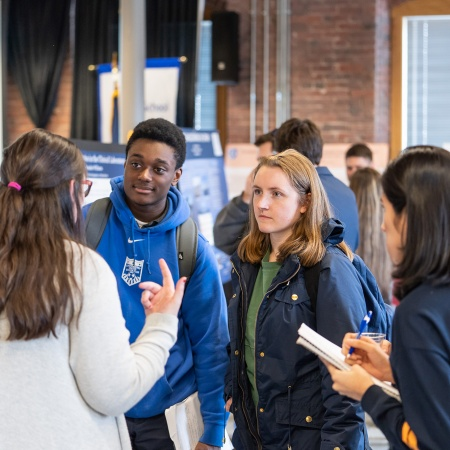 Students listening to a presenter describe her research during the UNH Manchester Undergraduate Research Conference 2018