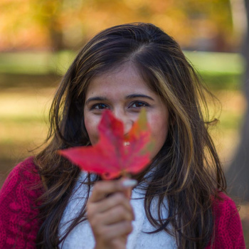 A UNH student holding a red leaf from a maple tree, with golden hues of foliage in the background