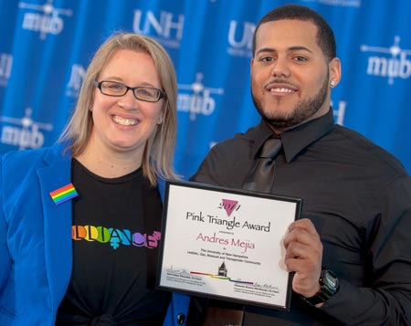 Andres Mejia is presented the Pink Triangle award by Shannon Brown-Marthouse