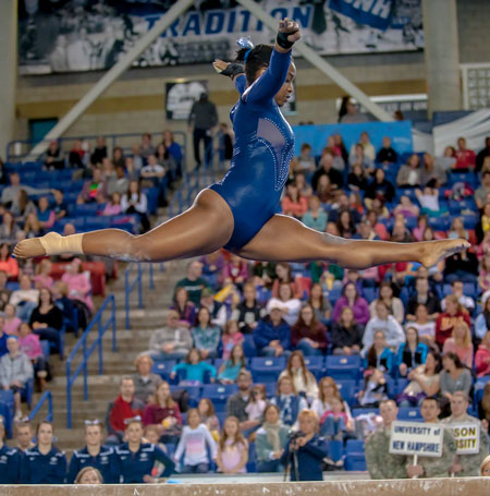 Gymnast Adrienne Hill split over the balancing beam
