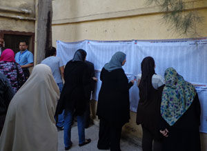 Egyptians in a polling center reviewing results.