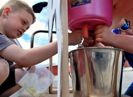 children milking an artificial cow's udder at the CREAM open house