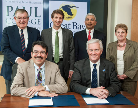 Great Bay Community College President Wildolfo Arvelo, seated from left, and University of New Hampshire President Mark Huddleston, celebrate the signing of an articulation agreement between the two institutions Wednesday, June 5, 2013. Pictured behind them, from left to right, are Paul Holloway, chairman of the Community College System of New Hampshire Board of Trustees; Ross Gittell, chancellor of  the Community College System of New Hampshire; Venky Venkatachalam, associate dean at the UNH Paul College; and Diane King, dean of academic affairs  at Great Bay Community College.