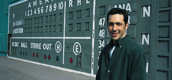 Christian Elias '95 in front of the Green Monster scoreboard