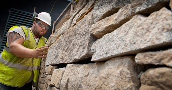 Mason from Stoneage Stoneworks construct a granite wall at the base of Paul College