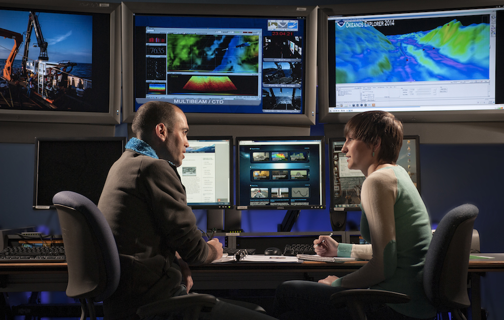 Two scientists looking at screens of seafloor