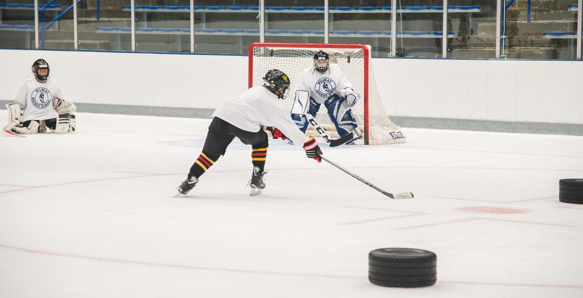 Player shooting puck at UNH Hockey Camp