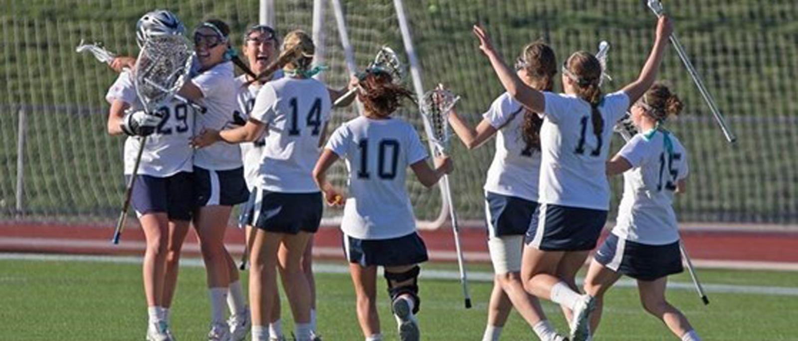 UNH Women's Lacrosse team celebrating a goal